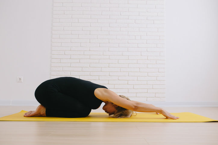 A woman doing child's pose (yoga) to relieve lower back pain